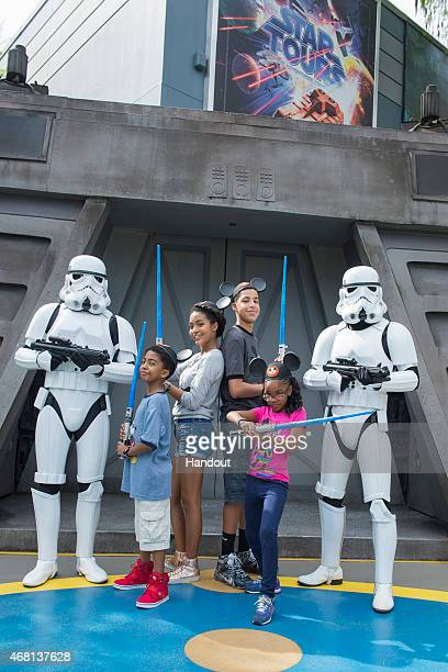 """In this handout image provided by Disney Parks, Marcus Scribner and Marsai Martin, from the cast of the ABC series """"black-ish,"""" wield their..."""