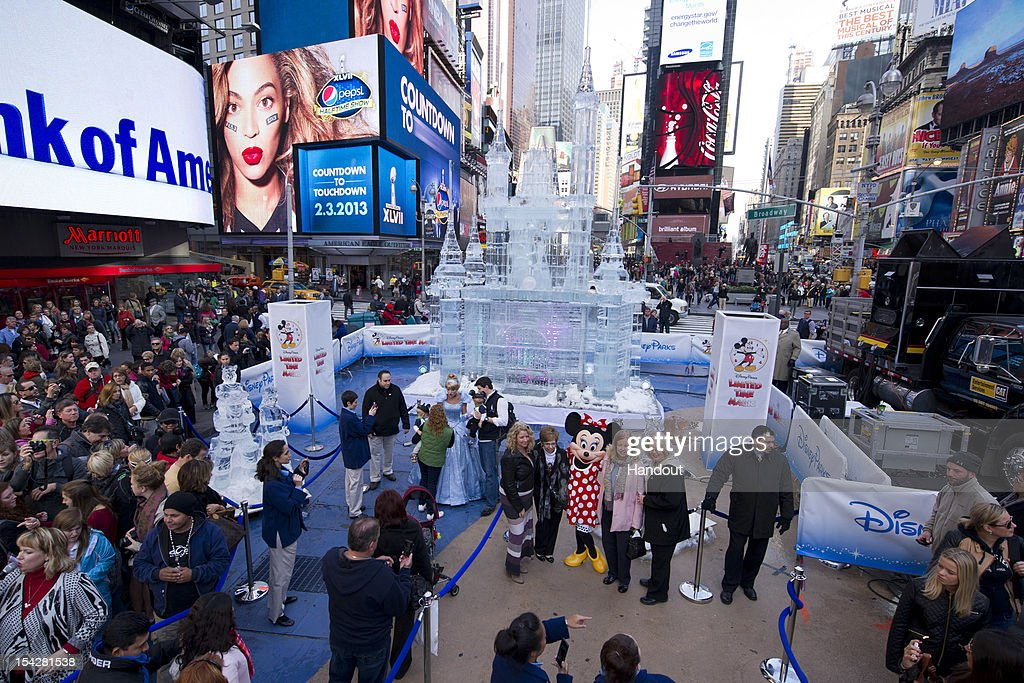 In this handout image provided by Disney Parks, Minnie Mouse poses for a photo in Times Square with passers-by. Disney Parks unveiled a 25-foot-tall, 45,000-pound castle made of ice as the sun rose over Times Square October 17, 2012 in New York City. The icy structure was unveiled during the Disney Parks announcement of 'Limited Time Magic' that will take place throughout 2013 at Disneyland Resort in California and Walt Disney World Resort in Florida. Next year, each week at the Disney theme parks will be highlighted by a different surprise or guest enhancement for a one-week-only engagement. Each weekly surprise, many never-before-seen in the Disney Parks, will include entertainment, dining, character experiences and more. Each one will disappear after seven days and make way for the next week's Limited Time Magic experience. The ice castle in Times Square -- which took more than 12 hours to construct and craft -- demonstrates the short-lived nature of Disney's Limited Time Magic.