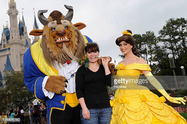 In this handout image provided by Disney Parks singer and former 'American Idol' champion Kelly Clarkson poses with Princess Belle and Beast from...