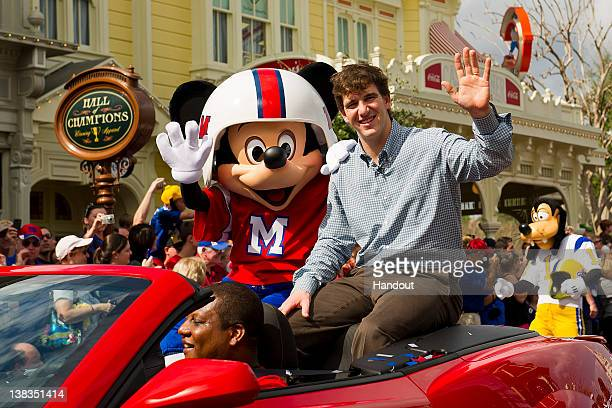 In this handout image provided by Disney Parks, Super Bowl XLVI MVP and New York Giants quarterback Eli Manning takes a celebratory ride with Mickey...