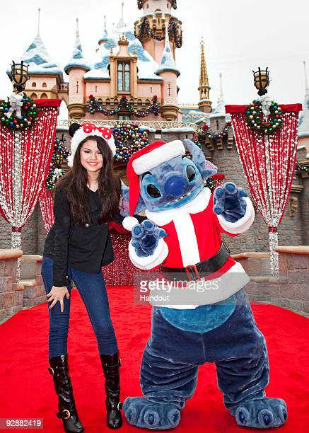 In this handout image provided by Disney Selena Gomez meets 'Santa' Stitch at Sleeping Beauty Winter Castle at Disneyland on November 7 2009 in...