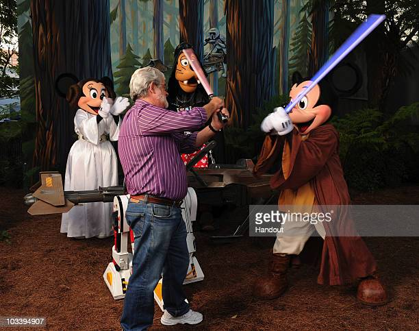 In this handout image provided by Disney Star Wars creator and legendary filmmaker George Lucas has a playful lightsaber duel Aug 14 2010 with Jedi...