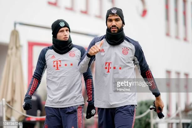 In this handout image provided by FC Bayern Muenchen arrive Benjamin Pavard with his team mate Eric Maxim ChoupoMoting for a training session at...