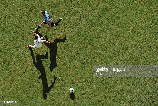 In this handout image provided by FIFA Alvaro Gonzalez of Uruguay competes with Mattia De Sciglio of Italy during the FIFA Confederations Cup Brazil...