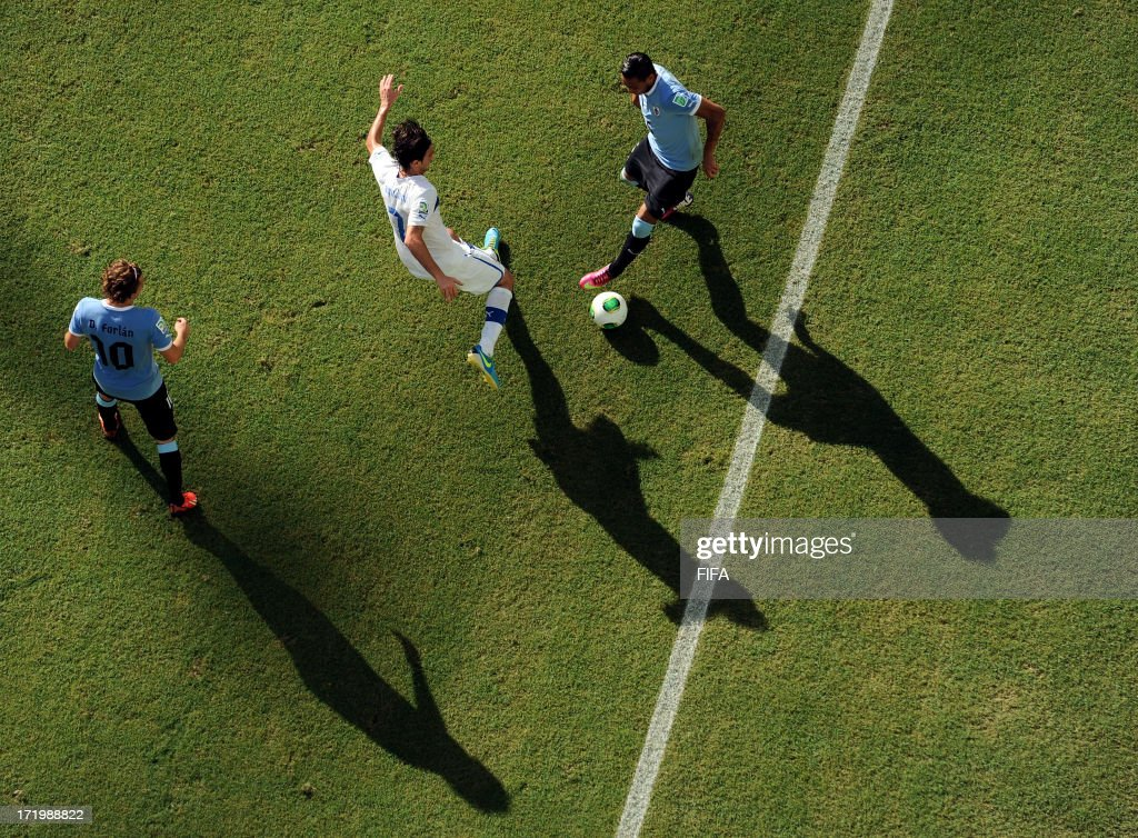 In this handout image provided by FIFA Alvaro Pereira of Uruguay competes with Alberto Aquilani of Italy during the FIFA Confederations Cup Brazil 2013 3rd Place match between Uruguay and Italy at Estadio Octavio Mangabeira (Arena Fonte Nova Salvador) on June 30, 2013 in Salvador, Brazil.