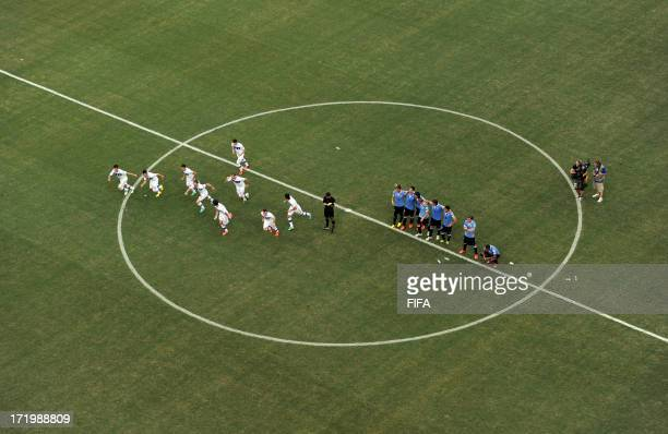 In this handout image provided by FIFA the Italy players celebrate after Gianluigi Buffon of Italy saved the penalty of Walter Gargano of Uruguay to...
