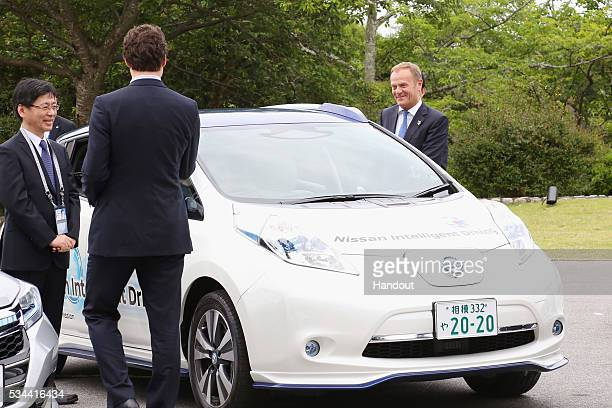 In this handout image provided by Foreign Ministry of Japan European Council President Donald Tusk rides the automated driving vehicle during the...