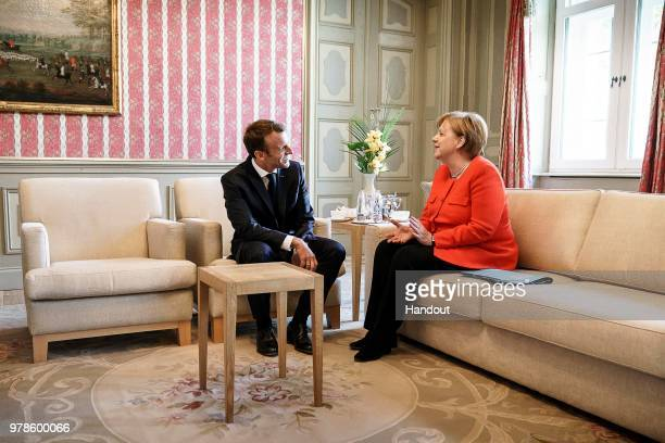In this handout image provided by German Government Press Office German Chancellor Angela Merkel speaks with French President Emmanuel Macron at...