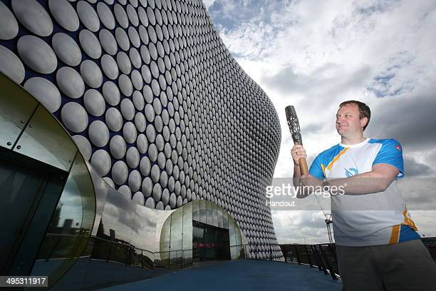In this handout image provided by Glasgow 2014 Ltd Adam Ruckwood from Marston Green holds the Queen's Baton outside the Bullring Shopping Centre as...