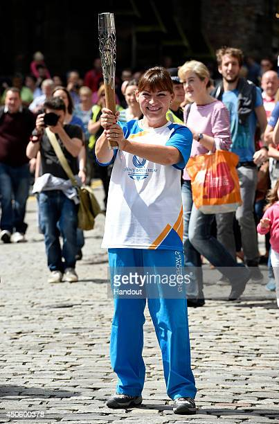 In this handout image provided by Glasgow 2014 Ltd Baton bearer 031 Lorraine Kelly carries the Glasgow 2014 Queen's Baton on June 14 2014 in...