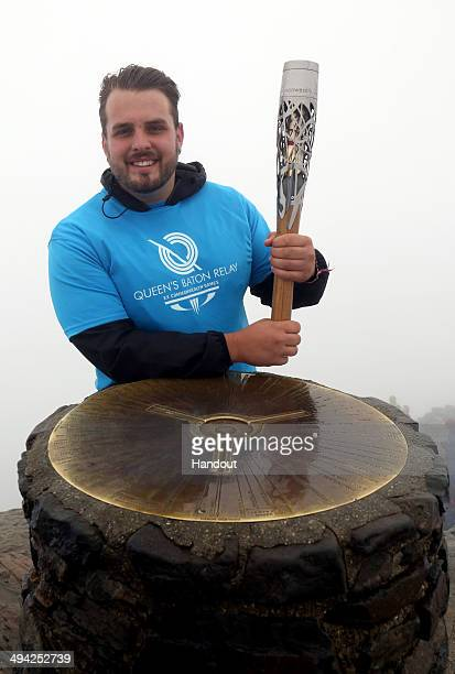 In this handout image provided by Glasgow 2014 Ltd Baton bearer and Paralympic Gold Medalist Aled Davies stands at the summit of Mount Snowdon with...
