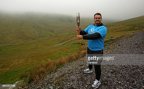 In this handout image provided by Glasgow 2014 Ltd Baton bearer and Paralympic Gold Medalist Aled Davies holds the Queen's Baton at the halfway point...