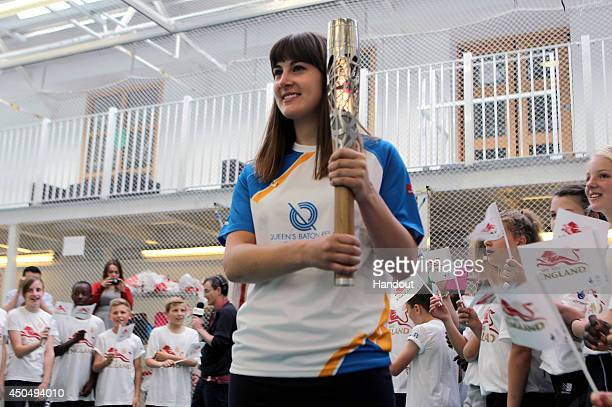 In this handout image provided by Glasgow 2014 Ltd Baton bearers Laura Beardsmore holds the Queen's Baton at the Yorkshire County Cricket Centre on...