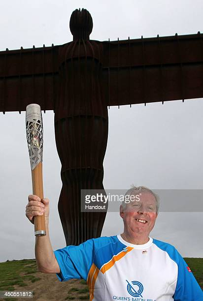 In this handout image provided by Glasgow 2014 Ltd Baton bearers Brendan Foster holds the Queen's Baton in front of the Angel of the North on June 13...