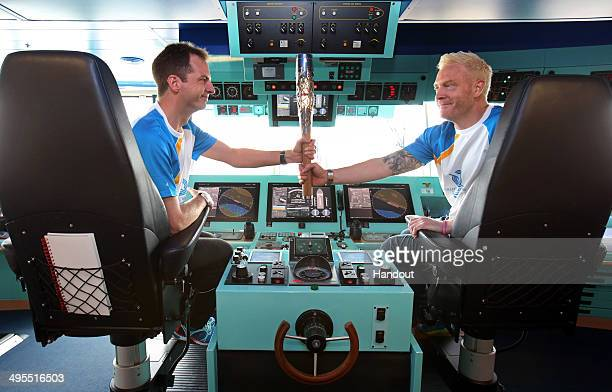 In this handout image provided by Glasgow 2014 Ltd Baton bearers James Saunders and Iwan Thomas hold the Queen's Baton on the bridge of Cunard's...
