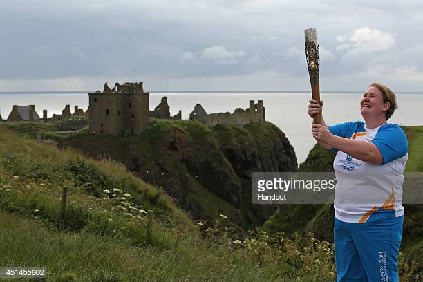 In this handout image provided by Glasgow 2014 Ltd, Batonbearer 004 Caroll Evans carries the Glasgow 2014 Queen's Baton at Dunnottar Castle in...