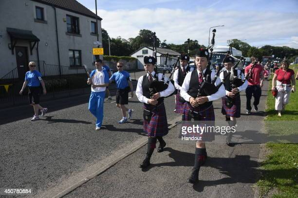 In this handout image provided by Glasgow 2014 Ltd Batonbearer 026 Josh Taylor carries the Glasgow 2014 Queen's Baton through Prestonpans in East...