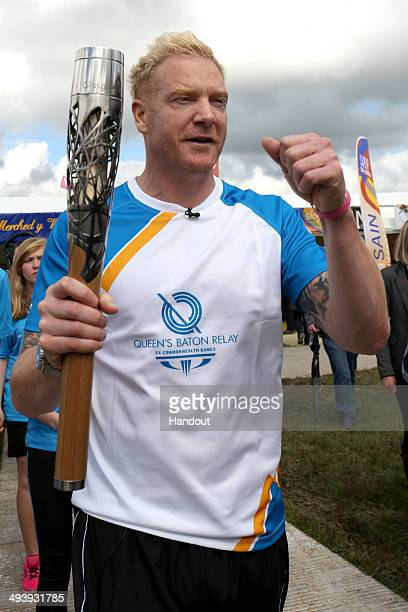 In this handout image provided by Glasgow 2014 Ltd Former Welsh athlete Iwan Thomas holds the Queen's Baton during the Glasgow 2014 Baton Relay on...