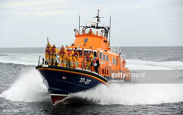 In this handout image provided by Glasgow 2014 Ltd, RNLI batonbearer Carl Cowie carries the Glasgow 2014 Queen's Baton in Moray during the Glasgow...