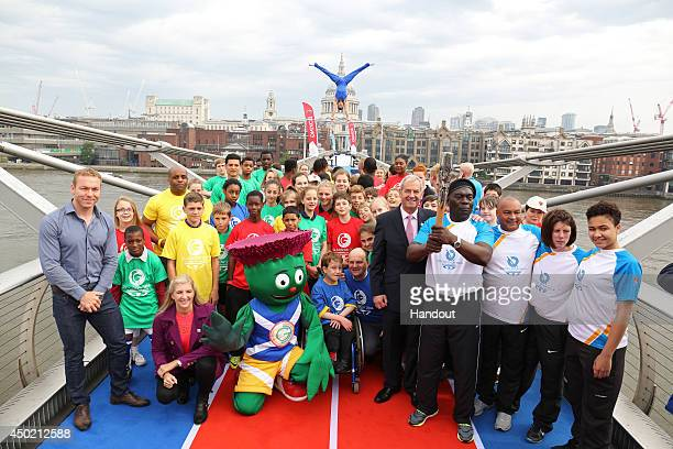 In this handout image provided by Glasgow 2014 Ltd Sir Chris Hoy Rebecca Adlington and Clyde the 2014 Games Mascot pose with baton bearers Carlton...