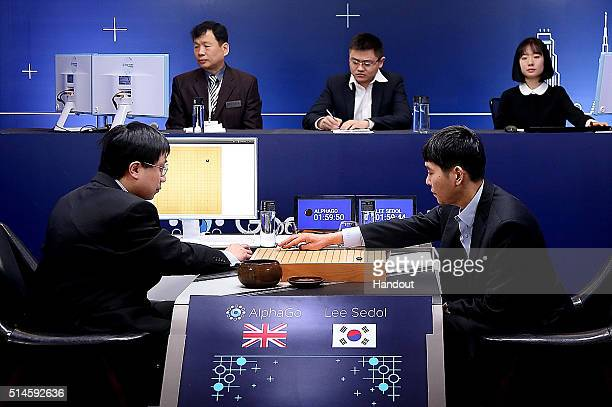 In this handout image provided by Google South Korean professional Go player Lee SeDol puts his first stone against Google's artificial intelligence...
