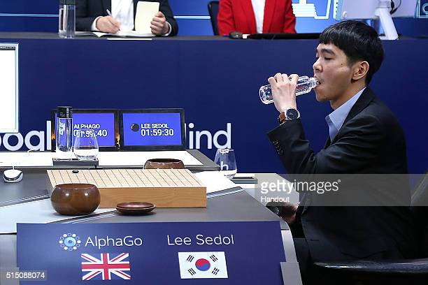 In this handout image provided by Google South Korean professional Go player Lee SeDol drinks water after puts his first stone against Google's...