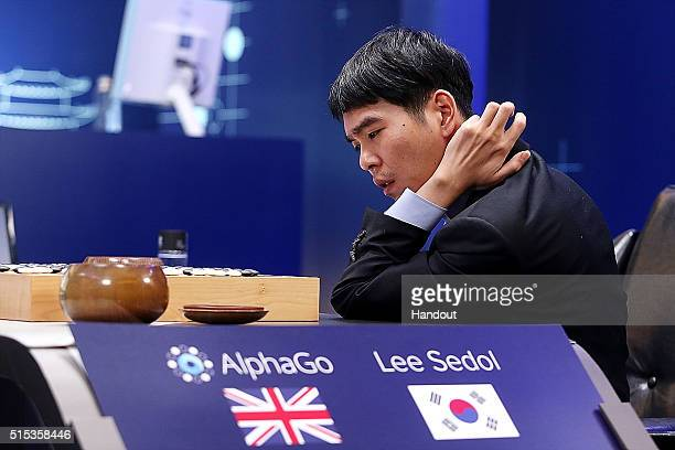 In this handout image provided by Google South Korean professional Go player Lee SeDol reviews the match after the fourth match against Google's...