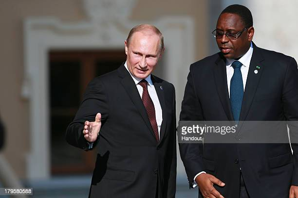 In this handout image provided by Host Photo Agency Russian President Vladimir Putin greets Senegalese President Macky Sall during an official...