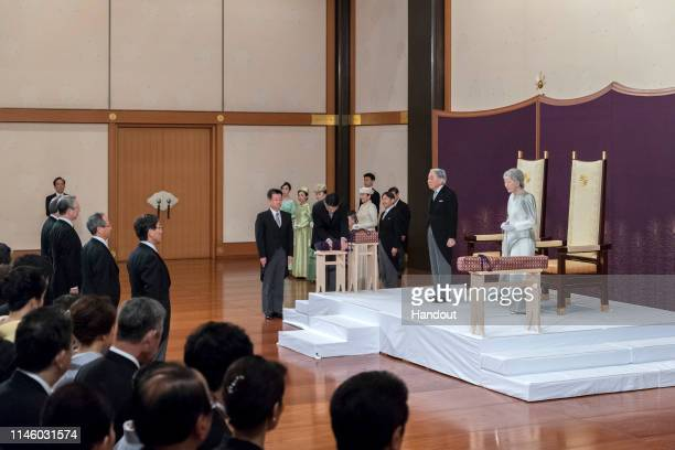In this handout image provided by Imperial Household Agency, Japanese Emperor Akihito and Empress Michiko listen to Prime Minister Shinzo during the...