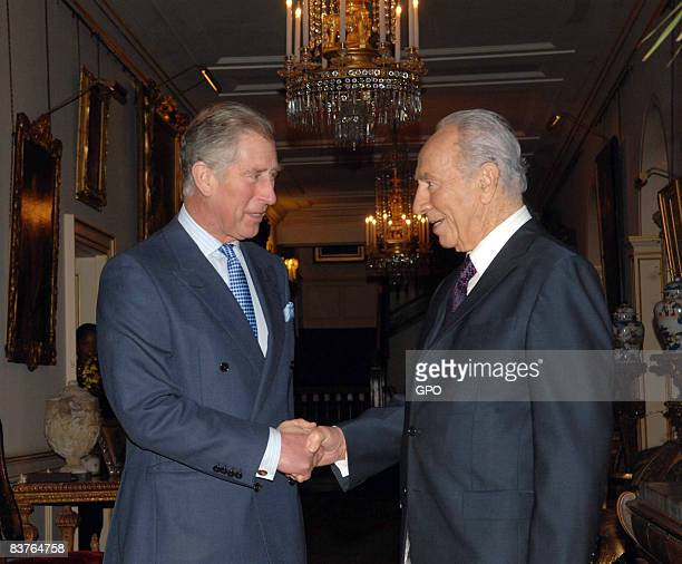 In this handout image provided by Israeli Government Press Office Israeli President Shimon Peres shakes hands with Prince Charles Prince of Wales at...