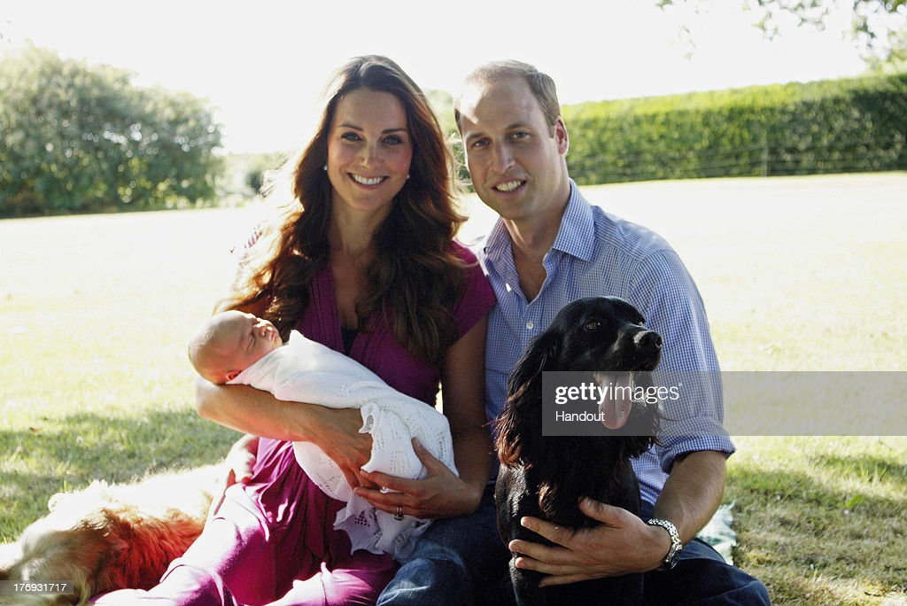 In this handout image provided by Kensington Palace, Catherine, Duchess of Cambridge and Prince William, Duke of Cambridge pose for a photograph with their son, Prince George Alexander Louis of Cambridge, surrounded by Lupo, the couple's cocker spaniel, and Tilly the retriever (a Middleton family pet) in the garden of the Middleton family home in August 2013 in Bucklebury, Berkshire.