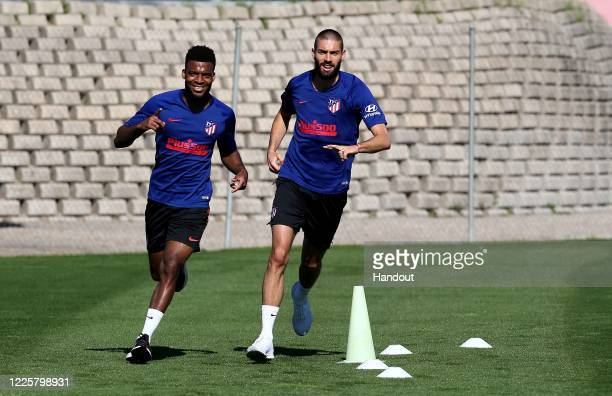 In this handout image provided by LaLiga, Thomas Lemar and Yannick Carrasco of Atletico de Madrid jog during a training session on May 19, 2020 in...