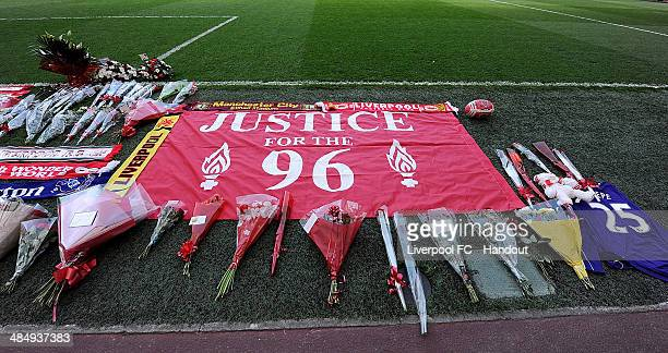 In this handout image provided by Liverpool FC a banner displaying the message 'Justice for the 96' rests on the turf next to wreaths and flowers...