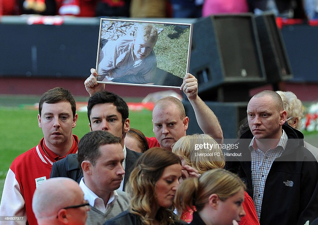 In this handout image provided by Liverpool FC, a man holds a picture of one of the 96 Hillsborough victims above his head during the 25th Hillsborough Anniversary Memorial Service at Anfield on April 15, 2014 in Liverpool, England.