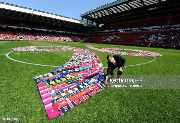 In this handout image provided by Liverpool FC Tom Werner part owner of Liverpool lays a scarf down in the middle of the pitch during the memorial...