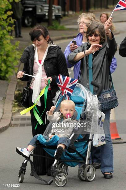In this handout image provided by LOCOG a young child waves a Union Jack flag at the roadside on the Torch Relay leg through Nottingham on Day 42 of...
