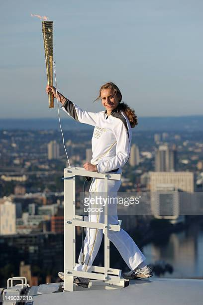 In this handout image provided by LOCOG Amelia HemplemanAdams poses with the Olympic Flame on top of a London Eye pod during Day 65 of the London...