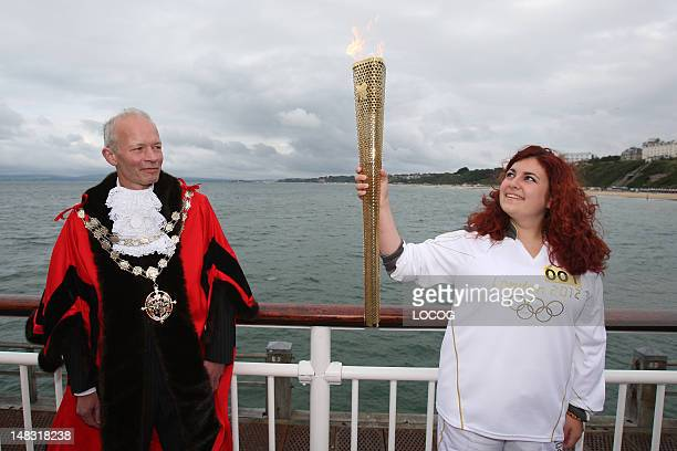 In this handout image provided by LOCOG Bournemouth Mayor Philip StanleyWatts looks on as Torchbearer 001 Mariam KazemMalaki carries the Olympic...