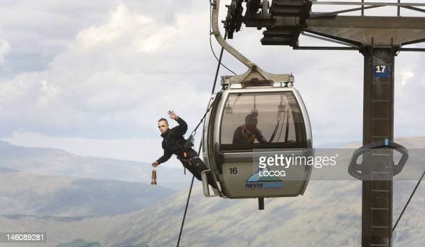 In this handout image provided by LOCOG Employee of the Nevis Range Davie Austin carries the Olympic Flame on a gondola on the Nevis Range on day 22...