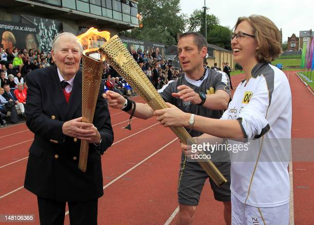In this handout image provided by LOCOG Former record breaking athlete Sir Roger Bannister passes the Flame to Torchbearer 001 Nicola Byrom on the...