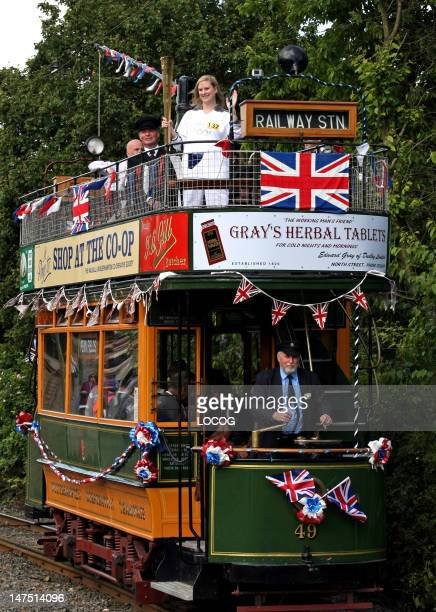 In this handout image provided by LOCOG Kate Macfarlane carries the Olympic Flame on the Black Country Living Museum tram on the Torch Relay leg...