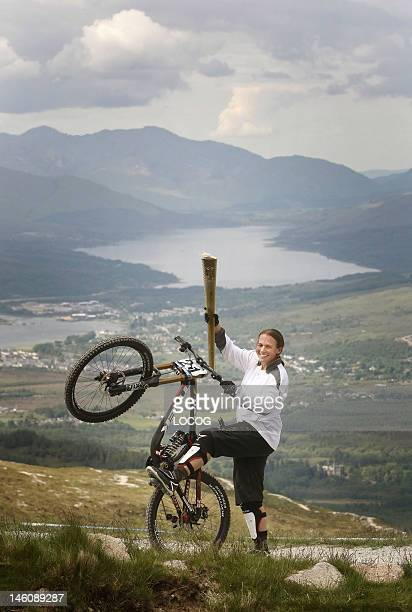 In this handout image provided by LOCOG Mountain Biker Tracy Moseley carries the Olympic Flame on the Nevis Range during day 22 of the London 2012...