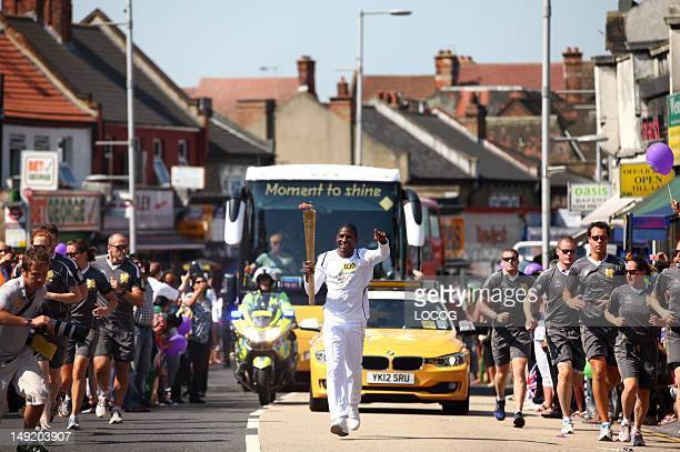 In this handout image provided by LOCOG Musician Labrinth carries the Olympic Flame on the Torch Relay leg between Harrow and Brent during Day 68 of...