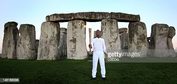 In this handout image provided by LOCOG Olympic gold medalist former sprinter Torchbearer 001 Michael Johnson holds the Olympic Flame at Stonehenge...