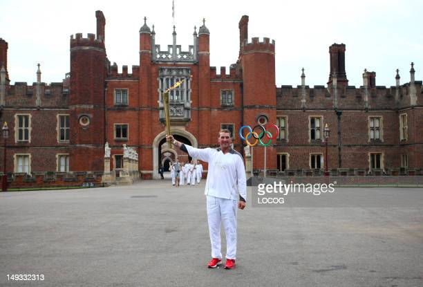 In this handout image provided by LOCOG Olympic Gold Medalist rower Torchbearer 011 Matthew Pinsent stands in front of the Great Gate at Hampton...