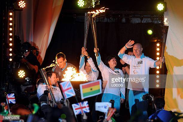 In this handout image provided by LOCOG, The cauldron is lit as the four Paralympic flames, which were lit on the UK's highest peaks, are united at...