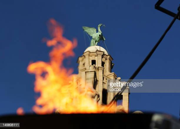 In this handout image provided by LOCOG The Olympic Flame burns in front of the Liver building following day 14 of the London 2012 Olympic Torch...