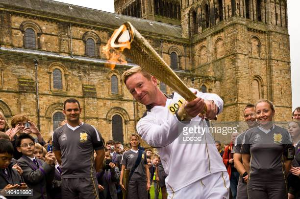 In this handout image provided by LOCOG Torchbearer 001 and cricketer Paul Collingwood carries the Olympic Flame on the Torch Relay leg between...