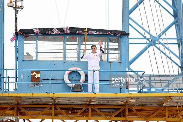 In this handout image provided by LOCOG Torchbearer 001 James Coupland holds the Olympic Flame on the Middlesbrough Transporter Bridge on June 18...