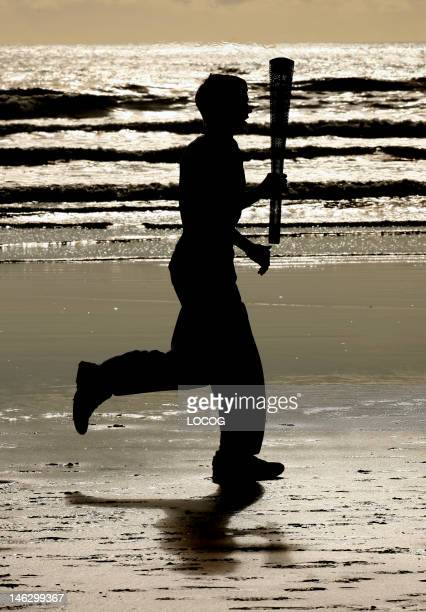 In this handout image provided by LOCOG Torchbearer 002 Joseph Forrest runs along West Sands beach with the Olympic Torch during the London 2012...